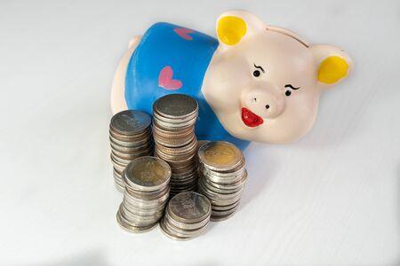 Ahorro de dinero con la hucha azul y la pila de monedas.