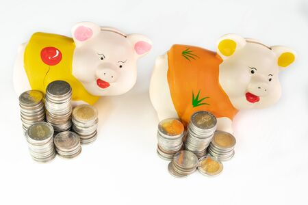 Yellow and Orange piggy bank saving money with coins pile.