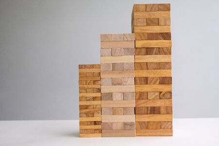Wood block tower with architecture model, Concept Risk of management and strategy plan, growth business success process and team work.