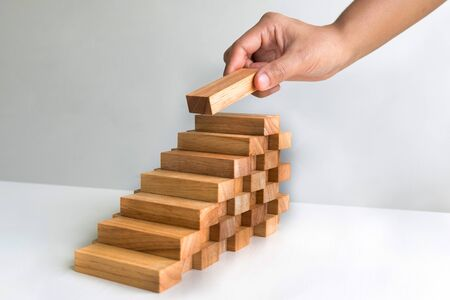 Hand holding blocks wood game, Concept Risk of management and strategy plan, growth business success process and team work.