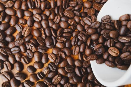 full of coffee beans spilling out white ceramic cup on brown wooden background.