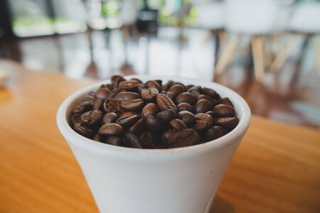 Coffee bean in white ceramic cup with brown wooden background 写真素材