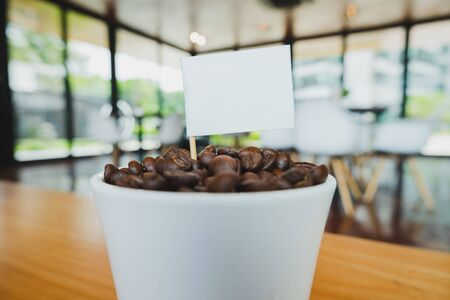 Coffee bean in white ceramic cup and white flag with brown wooden background. 写真素材