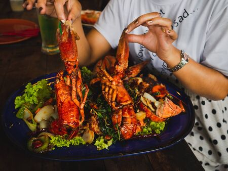 woman hand holding Fried shrimp with herb in blue dish ready for dinner.