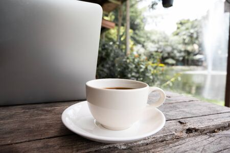 A cup of coffee on the wooden table behide laptop.