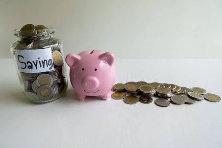 Glass and pink piggy bank with coins pile, step up growing business to success and saving for retirement  concept.