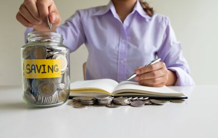 woman putting coin into glass piggy bank with pencil and Graph, step up growing business to success and saving for retirement  concept. Imagens