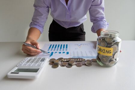 woman point to graph with glass piggy bank  and calculator, step up growing business to success and saving for retirement  concept.