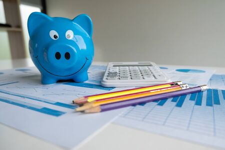 Blue piggy bank with pencils calculator and Graph, step up growing business to success and saving for retirement  concept. Imagens