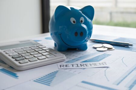 Blue piggy bank with pen calculator and Graph, step up growing business to success and saving for retirement  concept.