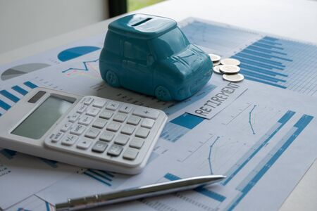 Car piggy bank with pen calculator and Graph, step up growing business to success and saving for retirement and Insurance concept.
