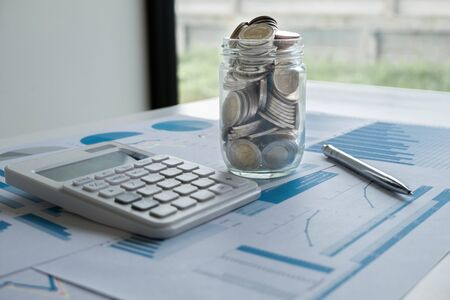 Glass bottle piggy bank with pen calculator and Graph, step up growing business to success and saving for retirement concept. Imagens