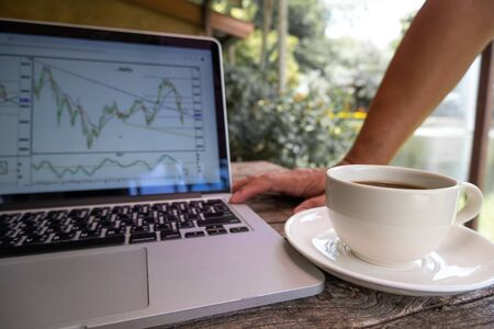 Trader man drink black coffee and pointing tactical move, strategy analysis of stock graph.