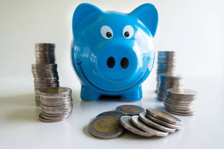 Blue piggy bank with coin pile, step up growing business to success and saving for retirement  concept. Imagens