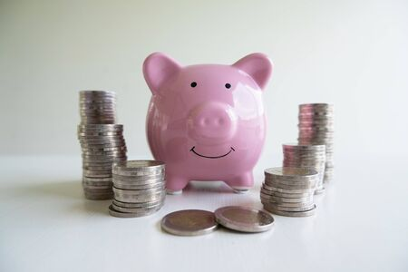 Pink piggy bank with coin pile, step up growing business to success and saving for retirement  concept.