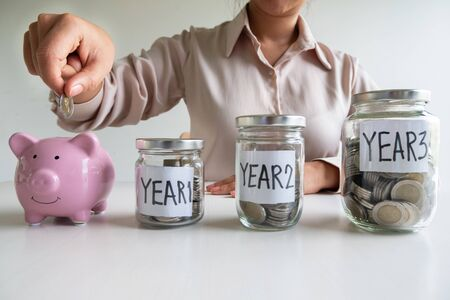 Business woman putting coin into pink piggy bank with 3 years planing account , step up growing business to success and saving for retirement  concept.