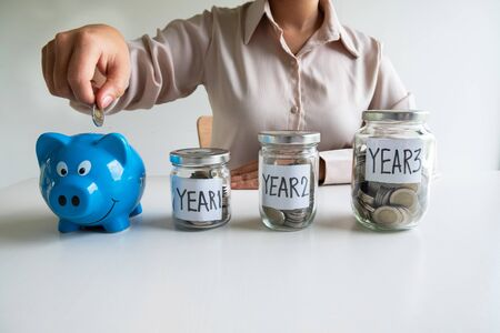Business woman putting coin into blue piggy bank with 3 years planing account , step up growing business to success and saving for retirement  concept.