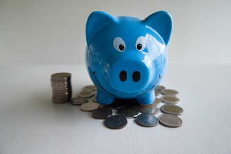 Blue piggy bank with coins pile, step up growing business to success and saving for retirement  concept. Imagens