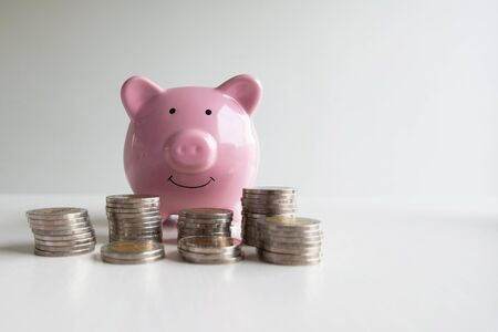 Pink piggy bank with coins pile, step up growing business to success and saving for retirement  concept.