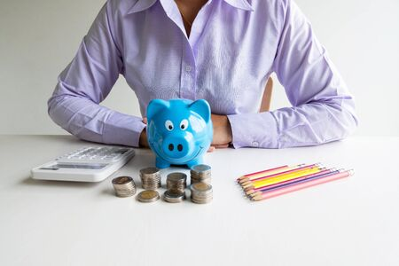 blue piggy bank with coins pile stand in front of business woman, step up growing business to success and saving for retirement  concept. Imagens