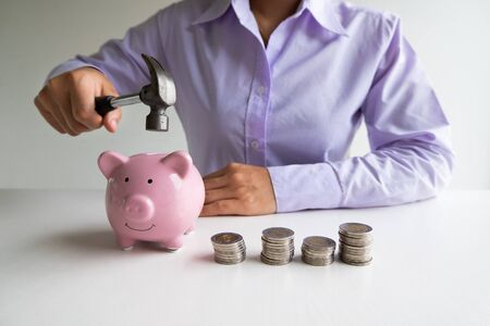 Business woman used hammer hide pink piggy bank with coins pile, step up growing business to success and saving for retirement  concept. Фото со стока