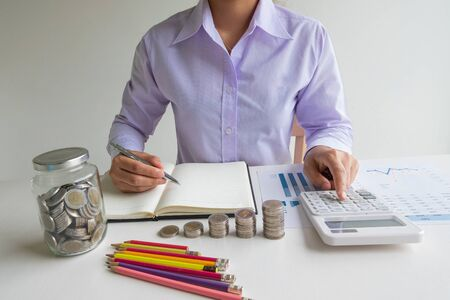 Business woman used calculator and record account with glass piggy bank, step up growing business to success and saving for retirement  concept.