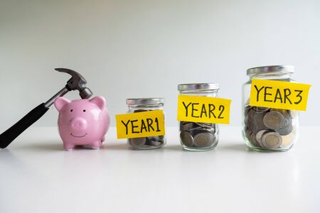 pink piggy bank and hammer with 3 years saving money plan, step up growing business to success and saving for retirement  concept. Imagens