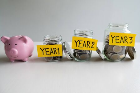 pink piggy bank with 3 years saving money plan, step up growing business to success and saving for retirement  concept.