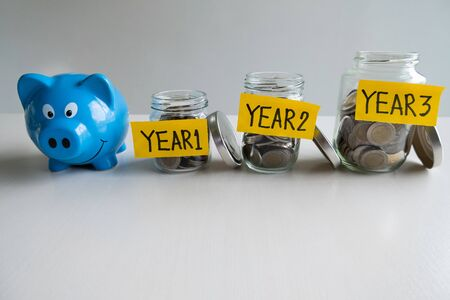Blue piggy bank with 3 years saving money plan, step up growing business to success and saving for retirement  concept.