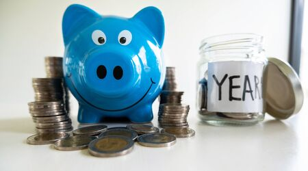 Blue piggy bank with coin pile, step up growing business to success and saving for retirement  concept. 写真素材