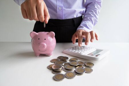 woman putting coin into pink piggy bank with coins pile, step up growing business to success and saving for retirement  concept.