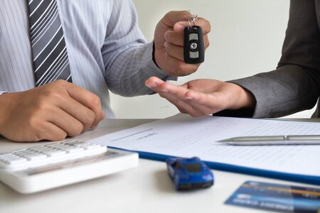 Car dealership provides advice about insurance details and car rental information and delivers the keys after signing the rental contract.