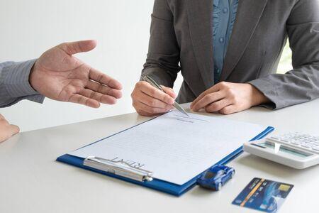 Concessionaria auto fornisce consulenza sui dettagli assicurativi e informazioni sull'autonoleggio e consegna le chiavi dopo aver firmato il contratto di noleggio.