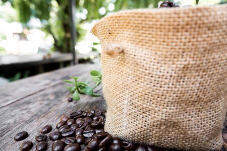 full of coffee beans spilling out bag on brown wooden background.