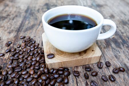 full of coffee beans spilling out bag on brown wooden background with a cup of black coffee. Stock fotó