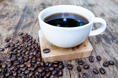 voller Kaffeebohnen, die Tasche auf braunem Holzhintergrund mit einer Tasse schwarzem Kaffee verschütten. Standard-Bild