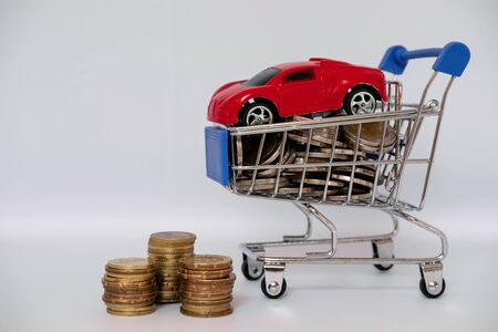 A barrow small shopping cart with coins on a white background for economizing  buying cars Concept of economizing and buying cars.