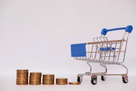 A small cart with a coin on a white background leading to growth to success, saving, saving concept. Reklamní fotografie