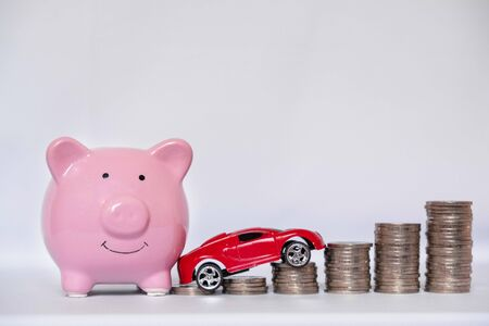 Piggy bank with coins on a white background to save on car buying, the concept of saving and buying cars.