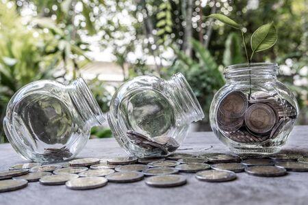 Glazen pot spaarvarken met munten. Plan uw spaargeld, run een groeiend bedrijf voor succes en spaar voor uw pensioen.