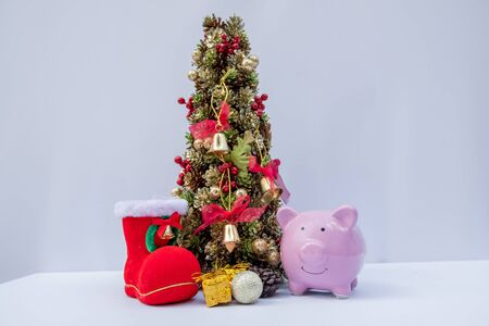 piggy bank and Beautifully decorated Christmas tree with a holiday party beginning in the new year and crossing to year 2020.