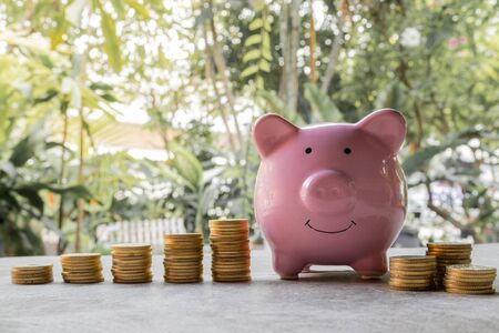 Pink piggy bank and golden coins pile on wooden table with the natural background, step up growing business to success and saving for retirement concept.