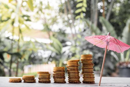 Coins and umbrellas in the natural background on a wooden table are a step towards success in saving and saving for retirement.