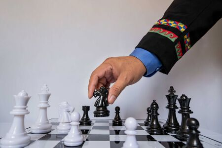 hand of businessman moving chess in competition, shows leadership, followers and business success strategies.