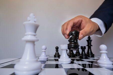 ręka biznesmena poruszającego się w szachy w konkurencji, pokazuje przywództwo, zwolenników i strategie sukcesu biznesowego.