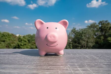 Pink piggy bank on black wooden with blue sky background, step up growing business to success and saving for retirement concept.
