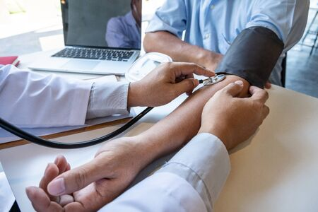 The male doctor measured blood pressure, the patient examined the heartbeat and talked about health care closely. Banque d'images