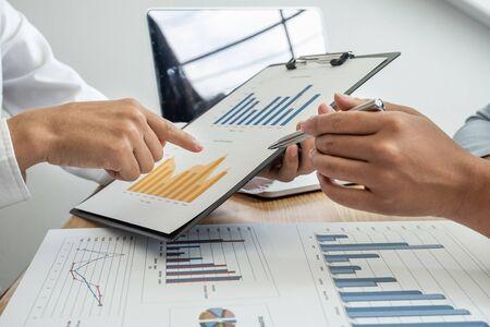 Zwei Geschäftsleiter diskutieren die Diagramme und Grafiken, die die Ergebnisse zeigen, und planen, eine neue Strategie für großen Erfolg zu starten. Standard-Bild