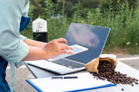 The woman inspected the coffee bean quality and recorded the results. Banco de Imagens
