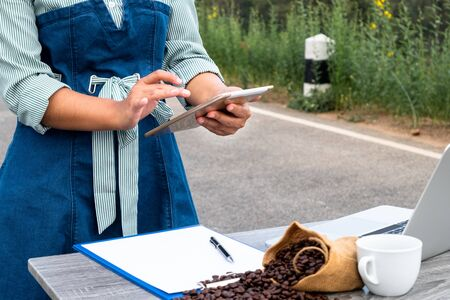 The woman inspected the coffee bean quality and recorded the results.